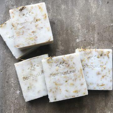 Oat, Chamomile & Calendula Hand & Body Soap Scrub Stacked on a Stone shelf