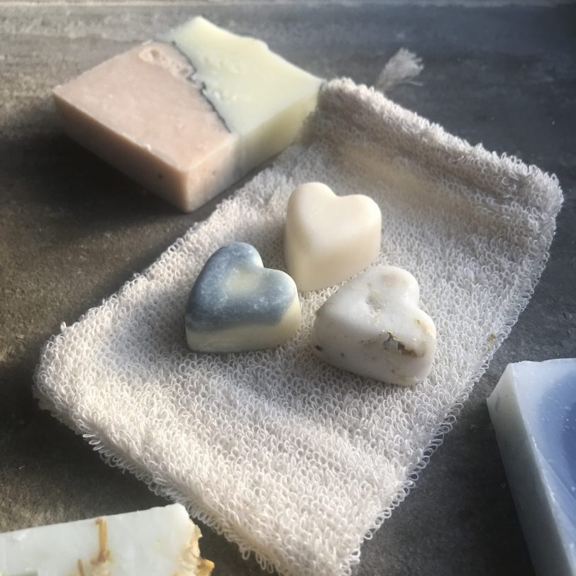 Organic unbleached cotton soap pouch with 3 travel sized soaps on top
